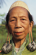 DAYAK, MALAYSIA. Sarawak, Borneo, South East Asia. Portrait of Dayak woman with distended earlobes and earings. Tropical rainforest and one of the world's richest, oldest eco-systems, flora and fauna, under threat from development, logging and deforestation. Home to indigenous Dayak native tribal peoples, farming by slash and burn cultivation, fishing and hunting wild boar. Home to the Penan, traditional nomadic hunter-gatherers, of whom only one thousand survive, eating roots, and hunting wild animals with blowpipes. Animists, Christians, they still practice traditional medicine from herbs and plants. Native people have mounted protests and blockades against logging concessions, many have been arrested and imprisoned.