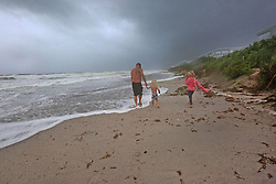In about 40 mph winds, an ominous sky to the south looms as Dennis Poley, 44, left, Axl Poley, 5, center and Tegan Poley, 7, of South Patrick Shores conducts a wave in Brevard County on Sunday, September 10, 2017 as Hurricane Irma made landfall in the state of Florida. Photo by Red Huber/Orlando Sentinel/TNS/ABACAPRESS.COM