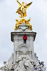 © Licensed to London News Pictures. 15/03/2019. LONDON, UK. A student climbs the Queen Victoria Memorial by Buckingham Palace. Thousands of students take part in a Climate Change strike in Parliament Square, marching down Whitehall to Buckingham Palace.  Similar strikes by students are taking part around the world demanding that governments take action against the effects of climate change.  Photo credit: Stephen Chung/LNP
