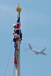© Licensed to London News Pictures. 18/06/2015. London, UK. A plane flying pas in the background as the flagpole at Buckingham palace is inspected. Photo credit: Ben Cawthra/LNP