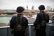 Sailors from the Chinese Naval assault ship Chang Bai Shan look across to Nelson's flagship, HMS Victory, and the Mary Rose Museum at Portsmouth Royal Navy Base today. The ship is involved in the first visit by the Chinese Navy to the UK since 2007 and the largest ever. She is accompanied by the frigate Yun Cheng and the replenishment ship Chaohu. The ships arrived in Portsmouth 24 hours early due to the expected bad weather. The Royal Navy statement stated that the five day formal visit is aimed at enhancing military understanding between the UK and China. Picture date Monday 12th January, 2015.<br /> Picture by Christopher Ison. Contact +447544 044177 chris@christopherison.com