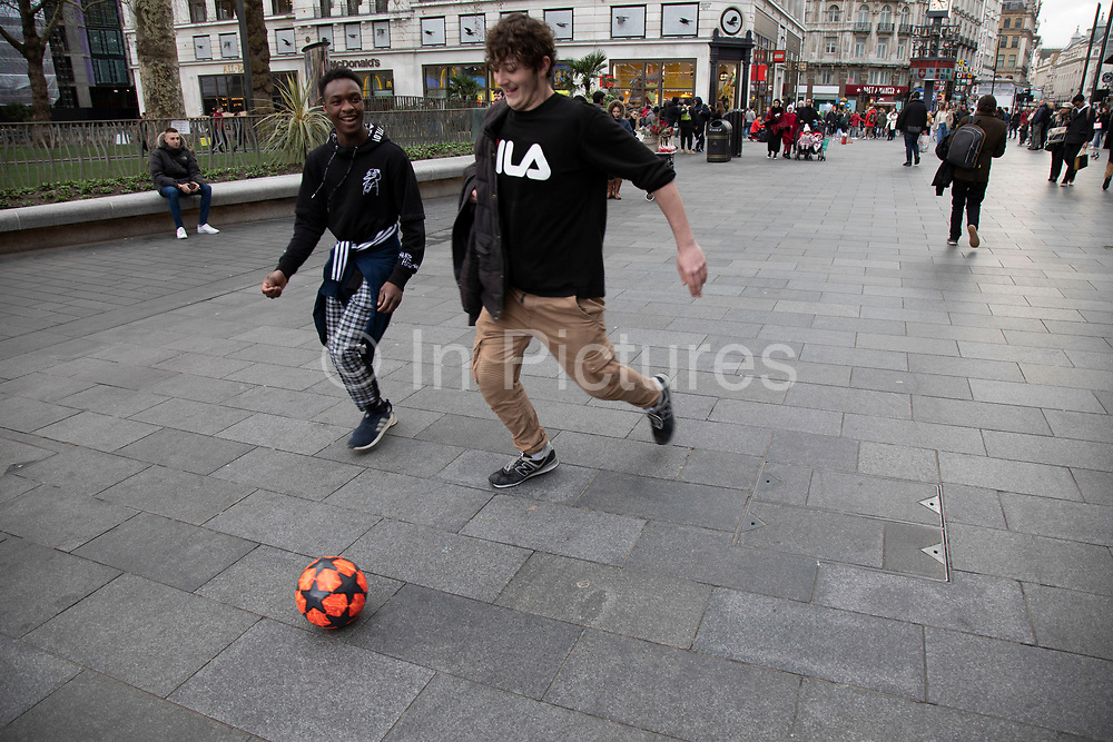 Young men playing football for fun on Leicester Square trying to scare passers by  in London, United Kingdom.