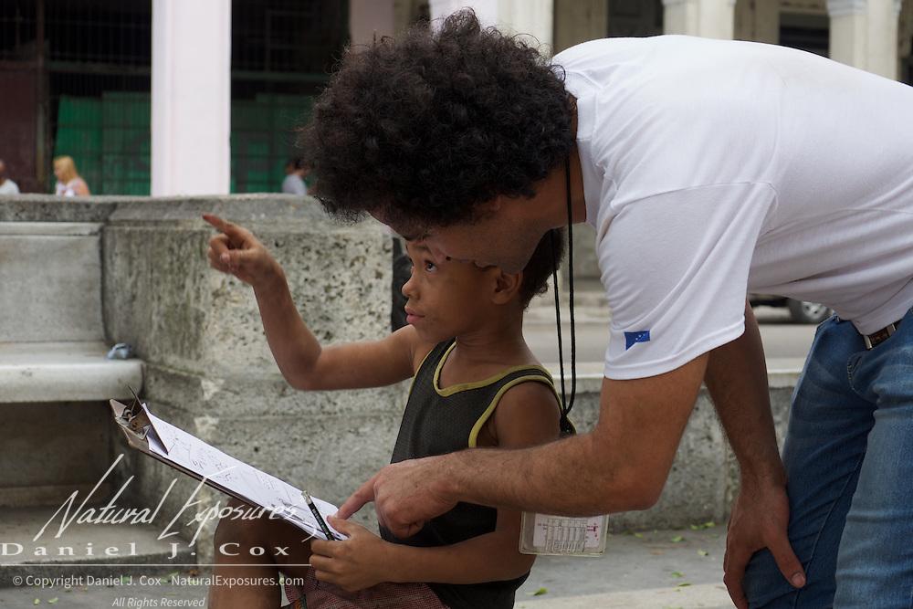 A little Cuban boy learning art from his adult friend and teacher on the Prado in Havana, Cuba.