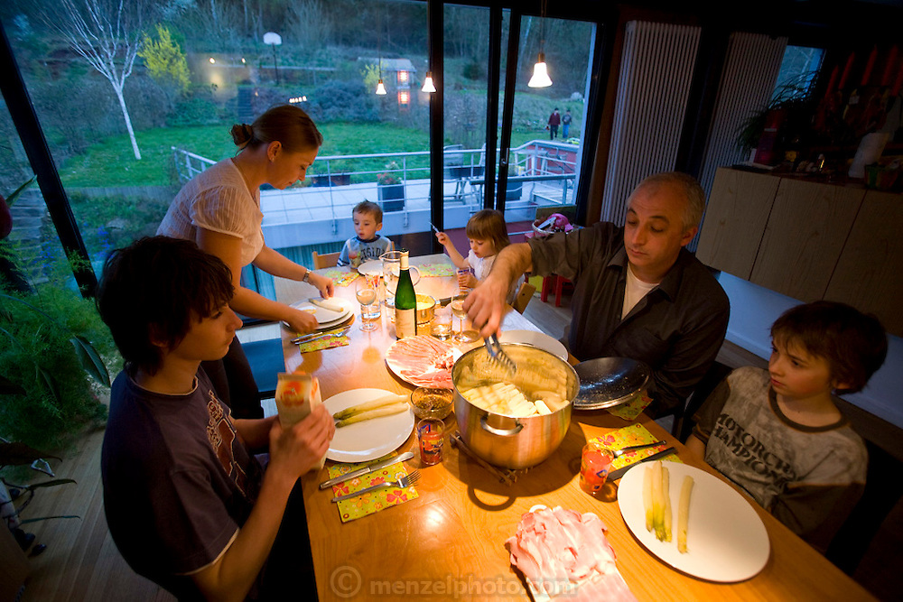 Architect Nico Engel and his wife Loba Anikina of Esch-sur-Alzette, southwestern Luxembourg, and their four children: Maxim, Lou, Mila, and Jora having supper. Grand Duchy of Luxembourg. Nico designed their home. Model Released. The image is part of a collection of images and documentation for Hungry Planet 2, a continuation of work done after publication of the book project Hungry Planet: What the World Eats.