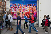 Group of children walk past a poster advertising a West End musical, London, UK.