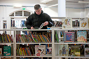 A man reads childrens titles in the re-opened Carnegie Library on Herne Hill in south London which has opened its doors for the first time in almost 2 years, on 15th February 2018, in London, England. Closed by Lambeth council and occupied by protesters for 10 days in 2016, the library bequeathed by US philanthropist Andrew Carnegie has been locked ever since because, say Lambeth austerity cuts are necessary. A gym that locals say they dont want or need has been installed in the listed basement and actual library space a fraction as before and its believed no qualified librarians will be present to administer it. Protesters also believe this community building will ultimately sold off by Lambeth council for luxury homes.