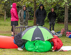 Licensed to London News Pictures. 23/05/2021. London, UK. Families get caught in the rain on Wimbledon Common in South West London as weather forecasters predict yet more rain and wind until this Wednesday as the miserable May Spring weather continues. However, sun is on the way for the May Bank Holiday with temperatures expected to hit 21c by the end of the month. Photo credit: Alex Lentati/LNP