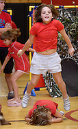 Middletown, NY -  An 8-year-old girl jumps over another girl in her group as YMCA summer camp children perform a play for their parents in the gymnasium on July 20, 2007..