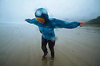 Young woman leaning into wind during storm on beach in Manzanita, Oregon.