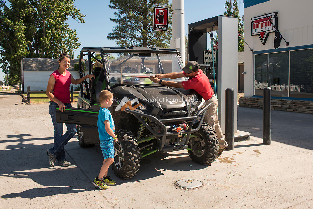 Father washing windshield on a Razor while mom and watch and chat while getting ready to ride ATVs in Oakley, Idaho. MR