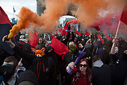Anarchists gather as a black bloc letting off smoke bombs for the Fuck Parade to party and protest at the class and wealth divide between rich and poor and the gentrification of London, the demonstration was organised by anarchist group Class War on May 1st 2016 in London, United Kingdom. The parade is now part of the May Day activism calendar as dissatisfaction about the establishment, the police and the inadequacy of the press is highlighted. Here the group shows it's anger, blocking traffic on Tower Bridge and shouting slogans. (photo by Mike Kemp/In Pictures via Getty Images)