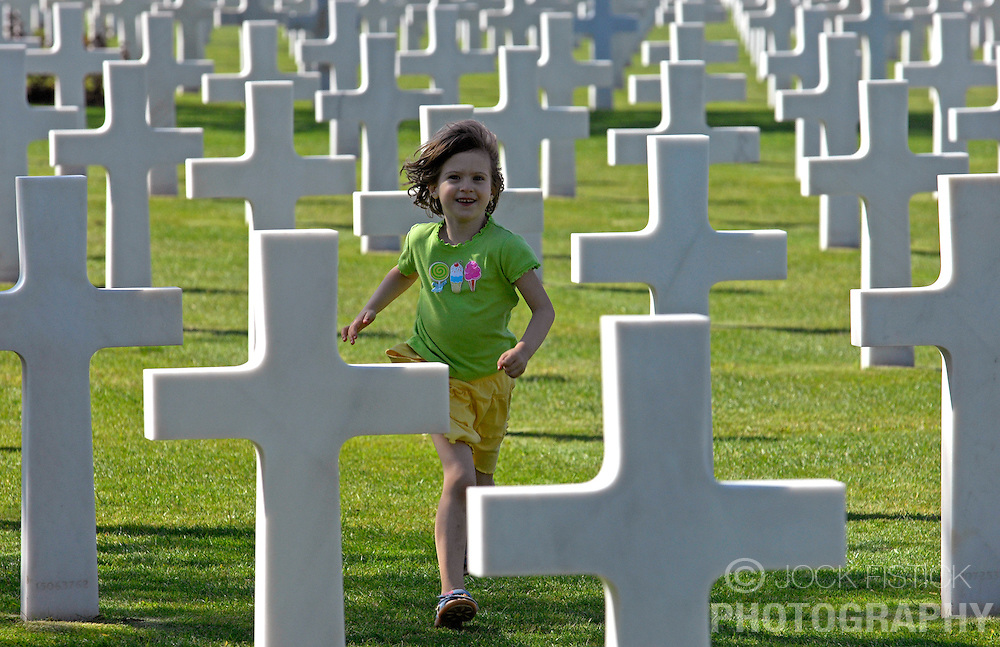 NORMANDY, FRANCE - A child runs between the grave markers at the American Cemetery at Omaha Beach where 9,387 service personnel are interred. Among the fallen are 3 Medal of Honor recipients four women and 307 unknown soldiers. Over one million visitors come to the cemetery to pay their respects every year. (Photo © Jock Fistick)