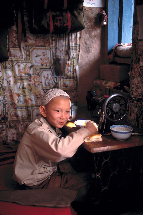 A young boy enjoys his lunchtime break in Kashgar, Xinjiang, China.