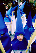 Young girl staring out from her blue silk hooded costume while taking part in the Semana Santa parade for Holy Week in Seville, Spain (Sevilla). They are carrying palm leaves.