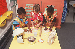 Multiracial group of nursery school children rolling out pastry using rolling pin and weighing scales,