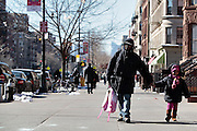 A father walks his daughter down Lenox Ave. after picking her up at school.  Harlem, a neighborhood of New York City in Manhattan, began as a Dutch village in 1658 and was later annexed to New York City in 1873.  At the beginning of the 20th century African-American's began arriving from the southern American states looking for work in the more industrious north.  With their migration, the African-American community brought with them a renaissance in the arts to Harlem that is still evident today.  After World War II Harlem began experiencing a significant rise in crime and poverty due to the Great Depression that lasted until the 21st century.  A new pride in the community has brought a renewed revival to Harlem, and crime rates have dropped to record lows giving the New York City neighborhood a new lease on life.