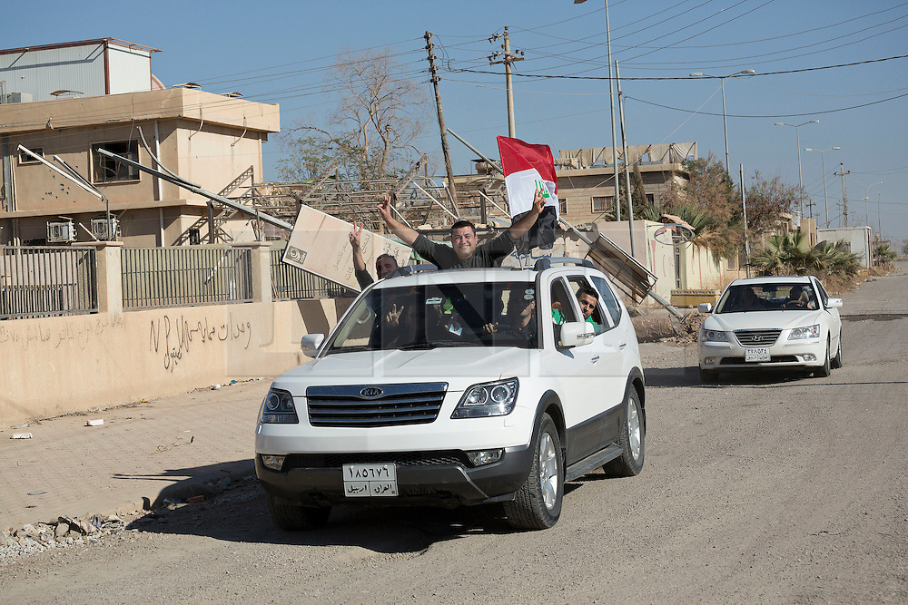 © Licensed to London News Pictures. 04/11/2016. Hamdaniyah, Iraq. Flying the Iraqi flag from their cars, Christian residents celebrate as they return to survey damage in the recently liberated Iraqi town of Hamdaniyah, Iraq.<br /> <br /> <br /> Although located close to a front line, littered with improvised explosive devices and pieces of unexploded ordnance the Christian town of Hamdaniyah has only recently been cleared of ISIS extremists who stayed behind to fight. After the town's liberation as part of the Mosul Offensive residents and priests of the town are now free to take short trips to assess damage, salvage possessions and clear up the mess left by militants during their two year occupation.<br /> <br /> Hamdaniyah, and much of the Nineveh plains, were captured by the Islamic State during a large offensive on the 7th of August 2014 that saw the extremists advance to within 20km of the Iraqi Kurdish capital Erbil. Residents of the town, who included many Christian refugees who escaped there after the fall of Mosul, were then forced to seek sanctuary in the Kurdish areas. In the year and two months of the ISIS occupation churches were burnt, homes were put into use as militant accommodation and bomb factories and some buildings destroyed by coalition airstrikes. Photo credit: Matt Cetti-Roberts/LNP