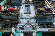 07 JUNE 2014 - YANGON, MYANMAR:  A residential building with shops on the ground floor on 22nd Street in Yangon. The building is one of a number of small colonial era buildings still in use in Yangon. This building, which doesn't have a name was opened in 1924. Yangon has the highest concentration of colonial style buildings still standing in Asia. Efforts are being made to preserve the buildings but many are in poor condition and not salvageable.   PHOTO BY JACK KURTZ