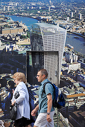 © Licensed to London News Pictures. 03/09/2013. London, UK. Pedestrians walk past a poster depicting a finished version of the 'Walky Talkie' building, also known as 20 Fenchurch Street, in London today (03/09/2013). The building, still under construction, has hit headlines after it was found that, due to it's curved architecture, light reflected from the building at certain times of the day was melting cars and has the ability to cook eggs. Photo credit: Matt Cetti-Roberts/LNP