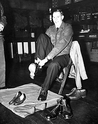 File photo dated 19-03-1957 of Dr Roger Bannister tries on a pair of Army boots as he receives his kit in the quartermaster's stores at the Queen Elizabeth Barracks, Crookham. He is starting his national service as a lieutenant in the Royal Army Medical Corps.
