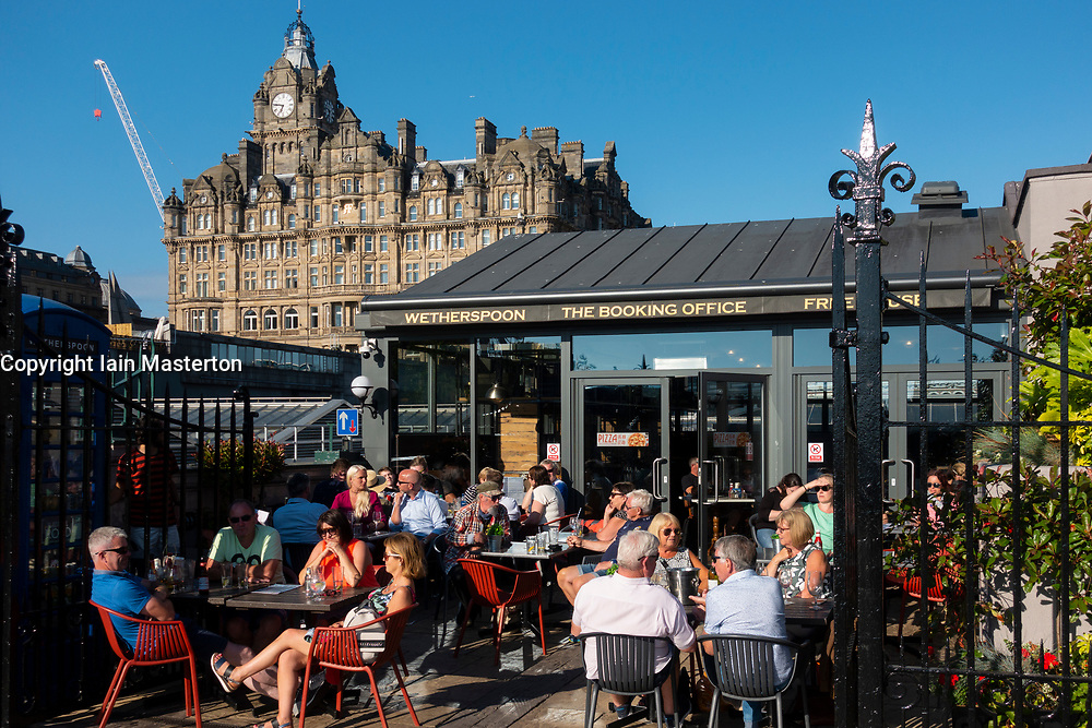 Busy Wetherspoon pub, The Booking Office, outdoor bar in summer at Waverley railway Station  in Edinburgh, Scotland UK