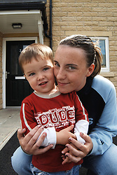 Young single mother and son in front of their new housing association house Yorkshire UK