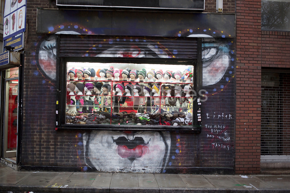 Wet day in Whitechapel in the East End of London, UK. Street art interacts with the open shutters of a cheap hat shop.
