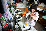 Seamstress making clothes in her small studio in an area just south of Tiananmen in Beijing, China. In this small Hutong street this small business woman makes clothes for individuals or parties on her own sewing machines and equipment. A small enterprise in a large city.