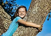 Girl hugging a tree.