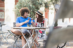 Young couple toasting wine glasses at outdoor restaurant