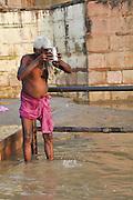 Holy man bathing in the Ganges river in Varanasi, Uttar Pradesh, India
