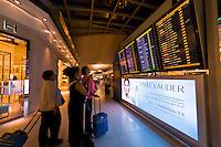 Travelers checking departure schedule, Suvarnabhumi International Airport, Bangkok, Thailand