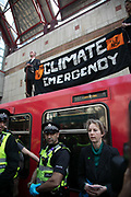Two activists climbed a DLR train at Canary Wharf station and one super glued himself to the carriage, 17th April 2019, Canary Wharf, London, United Kingdom. The environmental protest group Extinction Rebellion has called for civil disobedience and peaceful protest to force the British government to take drastic action on climate change. The group wants the governement to tell the truth and admit that the impact of climate change is much more severe than they say and that action to mitigate catastrophic climate change is urgent.