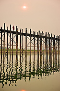 A monk crosses U Bein bridge, near Mandalay at sunset. The 1.2 km wooden footbridge (longest teak bridge in the world) was built by the mayor U Bein salvaging the unwanted teak columns from the old palace in Amarapura during the move to Mandalay.