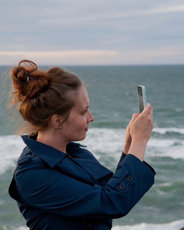 Woman using her phone to take a picture by the sea