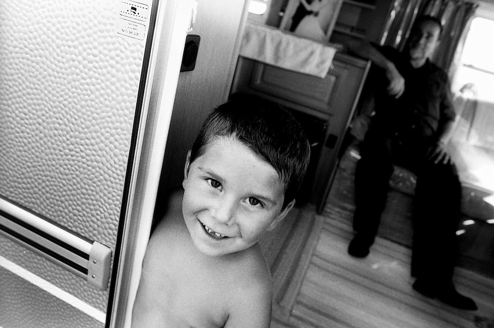 """Child with his father in their caravan. France, Marville, August 2002 - 40,000 Gypsies from all over the Europe come together and pray in Marville, a little village in France. They encamped in a former air base of NATO during 1 week. """"Vie et Lumiere"""" is an International Evangelic Community.©Jean-Michel Clajot / Cosmos"""