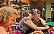 Bi-racial husband and wife hug as child sits close