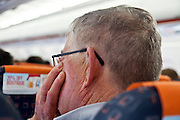senior man in an airplane with his head resting on his hand