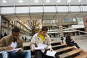 Two students study outside at London Metropolitan University's Holloway Road campus. Writing up notes and reading course work, the two young men sit on wooden steps with other students. London Metropolitan University is one of the foremost providers of undergraduate, postgraduate, professional and vocational education and training in Britain. Their courses are planned in consultation with employers and examining bodies in commerce, industry, the world of art and design, the financial services industries and other professions. To compare profiles, Oxford University has the lowest proportion of working-class students, with 11.5%. London Metropolitan University has the greatest proportion, with 57.2%. The first building, designed by Charles Bell, was opened in 1896.