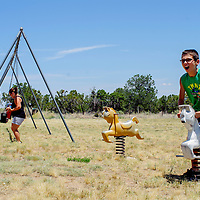 Logan Blain take a turn on the playground equipment behind the old schoolhouse during the Homesteaders Reunion Saturday in Fence Lake.