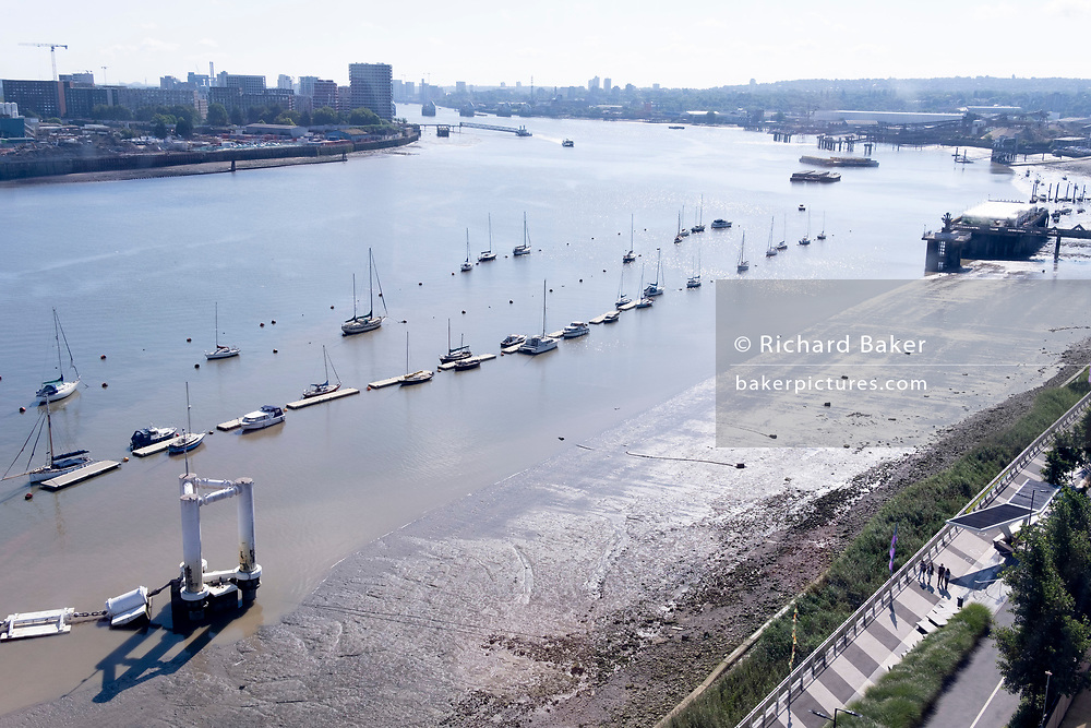 An aerial view from an Emirates Air Line cable car of yachts and other boat types moored on the River Thames opposite the Greenwich Peninsular, on 11th August 2021, in London, England.
