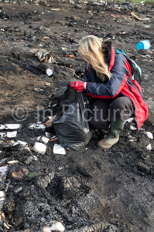 France. Refugees. Calais. So-called Jungle camp .  A volunteers from Britain helps clear up rubbish and mess from the fire the night before (Saturday  21st November 2015 )