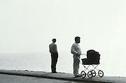 Two men with a baby carriage one standing at a distance