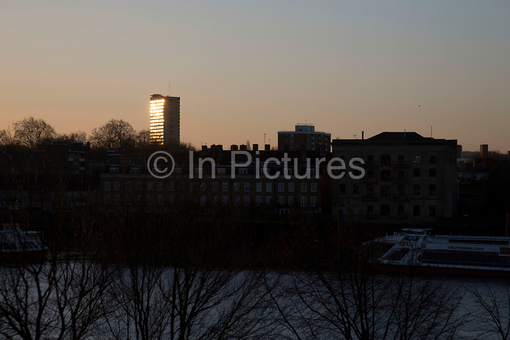 Sunrise reflected in a tower block in South East London, UK. From the same position about two days each year the sun lines up perfectly with this council block and reflects the rising sun directly.