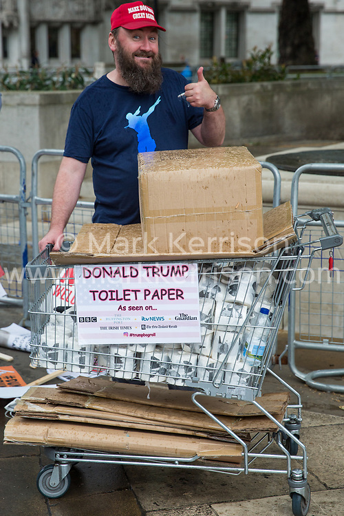 London, UK. 4 June, 2019. A man distributes Donald Trump toilet paper during a protest by thousands of climate change activists, women's groups, students, pacifists, trade union members and families against the state visit of US President Donald Trump on the second day of his three day visit. A large policing operation was in place to facilitate the protest but to prevent access to areas immediately adjacent to Downing Street, where talks were taking place between Prime Minister Theresa May and President Trump.