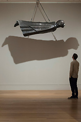 """© Licensed to London News Pictures. 04/06/2018. LONDON, UK. A gallery staff member views """"The Floating One, Der Schwebende"""", 1927, by Ernst Barlach at a preview of """"Aftermath:  Art in the wake of World War One"""" at Tate Britain.  The exhibition marks 100 years since the end of the First World War, exploring the impact of the conflict on British, German, and French art in over 150 works from 1916 to 1932.  The show runs 5 June to 23 September 2018.  Photo credit: Stephen Chung/LNP"""