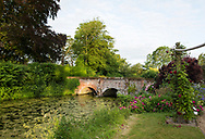 Early sun on a 16th century arched brick bridge over the moat surrounded by roses at Hindringham Hall, Hindringham, Norfolk, UK