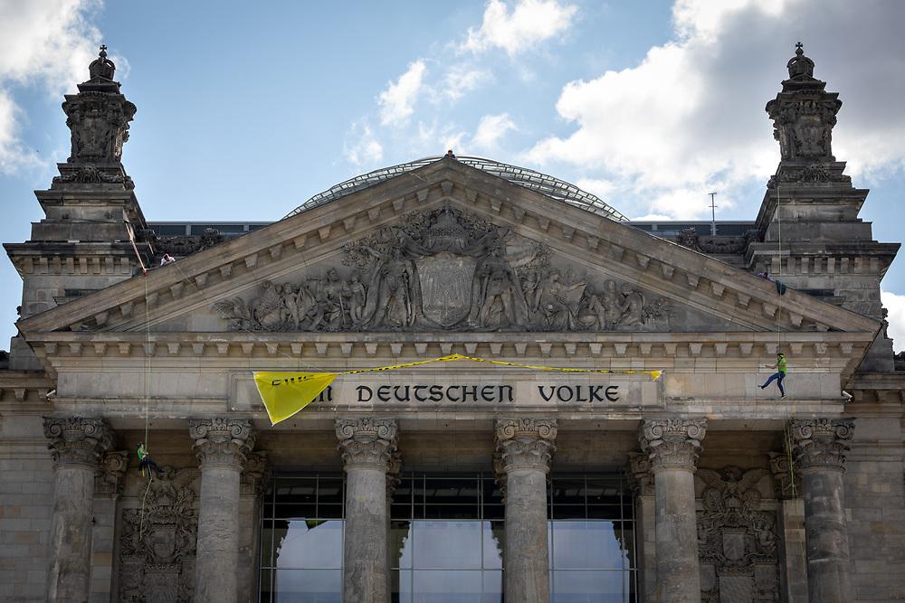 """Umwelt-Aktivisten von Greenpeace seilen sich vom Dach des Reichstagsgebäude in Berlin ab und spannen an der Fassade unter dem Schriftzug """"Dem deutschen Volke"""" ein Transparent """"eine Zukunft ohne Kohlekraft"""", um gegen das Kohleausstiegsgesetz und für einen sofortigen Kohleausstieg zu protestieren. <br /> <br /> [© Christian Mang - Veroeffentlichung nur gg. Honorar (zzgl. MwSt.), Urhebervermerk und Beleg. Nur für redaktionelle Nutzung - Publication only with licence fee payment, copyright notice and voucher copy. For editorial use only - No model release. No property release. Kontakt: mail@christianmang.com.]"""