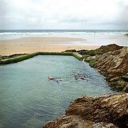 2 young women float in Chapel Rock Pool, Perranporth, Cornwall, UK. Until the 1950s and the rise of the heated indoor swimming pool, children learnt to swim outdoors. For those close to the sea, many man-made tidal swimming pools were constructed around Britain's coastline. Heated by the sun, these tidal pools were often built to keep bathers safe from high and rough seas, which explains why so many of them are clustered in Scotland and around the surfing beaches of Cornwall. Whether they are simple swimming holes made by shoring up natural rock pools or grand lido-like pools complete with lifeguards and tea huts, they are all refreshed by good high tides.