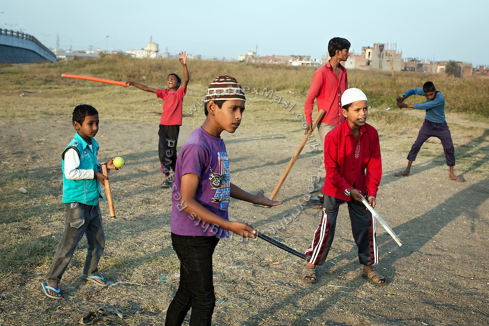 Boys are playing cricket by the side of a large evaporation pool once used by Union Carbide for their industrial wastewater, next to Blue Moon, the contaminated colonies next to the abandoned Union Carbide (now DOW Chemical) industrial complex, in Bhopal, Madhya Pradesh, central India. In this area, hazardous chemical have also been buried and continue to contaminate the underground aquifers.